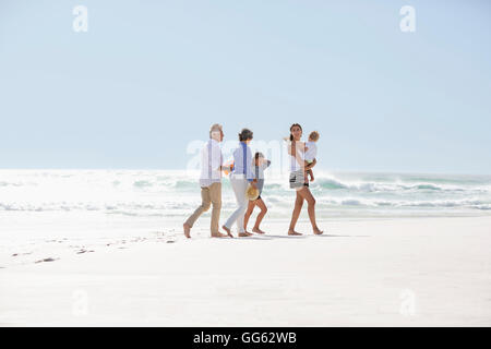 Multi-generation family walking on the beach - Stock Photo