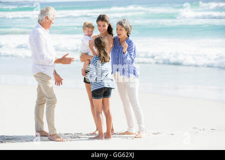 Multi-generation family standing on the beach - Stock Photo