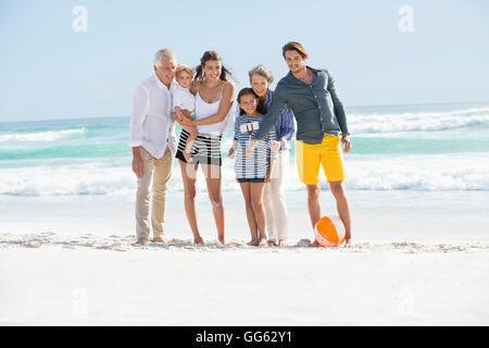 Multi-generation family standing on the beach taking selfie - Stock Photo