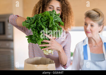 Senior woman with daughter in kitchen - Stock Photo