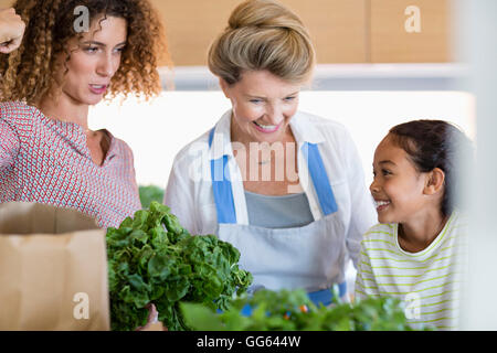 Senior woman with daughter and granddaughter in kitchen - Stock Photo