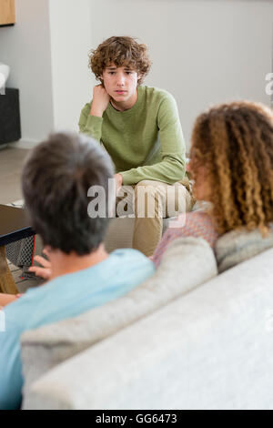 Family talking in a living room at home - Stock Photo