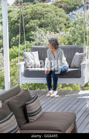 Happy woman relaxing on swing chair at porch - Stock Photo