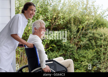 Female nurse assisting senior man in wheelchair on porch - Stock Photo