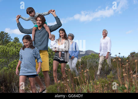 Happy multi-generation family walking on landscape - Stock Photo