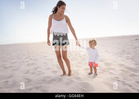 Happy mother with her little son walking on beach - Stock Photo