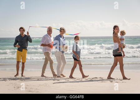 Happy multi-generation family enjoying on beach - Stock Photo