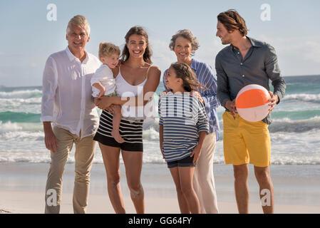 Portrait of happy multi-generation family standing on beach - Stock Photo