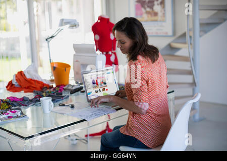 Fashion designer working on laptop in her office - Stock Photo
