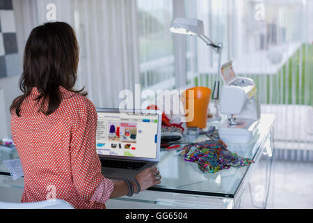 Rear view of female fashion designer working on a laptop - Stock Photo
