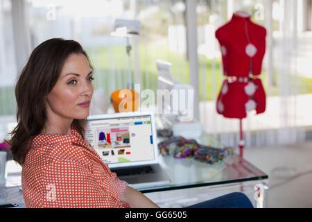 Female dress designer thinking in her studio - Stock Photo