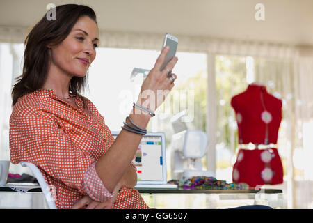 Female dress designer using a mobile phone - Stock Photo