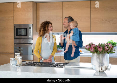 Happy couple standing in the kitchen with their daughter - Stock Photo