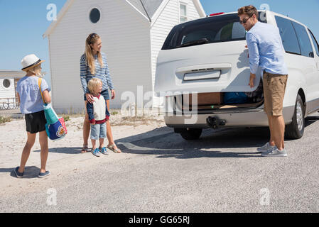 Young family packing car with beach gears for vacation - Stock Photo
