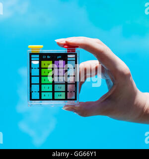 testing chlorine pollution in blue water of outdoor pool by chemical tester - Stock Photo