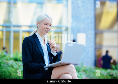 Businesswoman chatting in financial district - Stock Photo