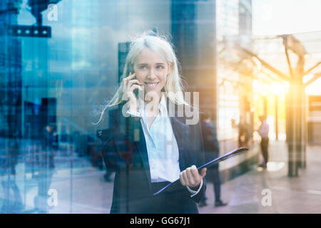 Businesswoman using a mobile phone - Stock Photo