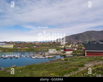 View across Tunulliarfik Fjord headland to Narsaq History Museum buildings with moored fishing boats Southern Greenland - Stock Photo