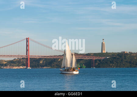 Sailboat navigating on the Tagus River near the Ponte 25 de Abril, Belem, Lisbon, Portugal, Europe - Stock Photo