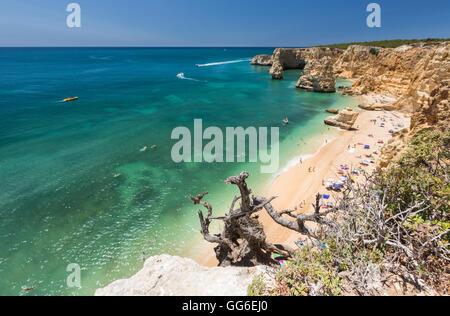 Tourists on sandy beach at Praia da Marinha surrounded by turquoise ocean, Caramujeira, Lagoa Municipality, Algarve, - Stock Photo
