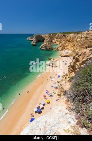 Tourists on sandy beach Praia da Marinha surrounded by turquoise ocean, Caramujeira, Lagoa Municipality, Algarve, - Stock Photo