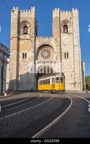 The yellow tram number 28 close to the ancient Cathedral (Se), Alfama district, Lisbon, Portugal, Europe - Stock Photo