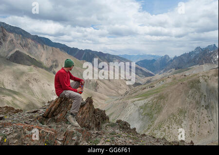 A trekker stops to admire the views from the top of the Konze La in the remote Himalayan region of Ladakh, India - Stock Photo