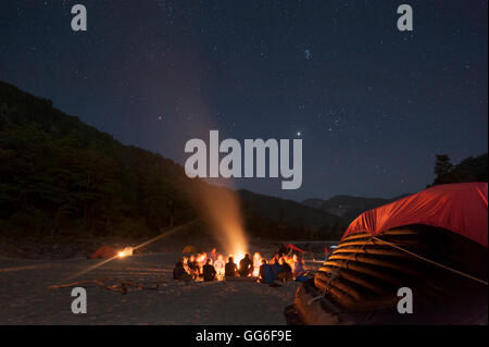 Sitting around a campfire next to the Karnali River during a rafting expedition in Nepal, Asia - Stock Photo