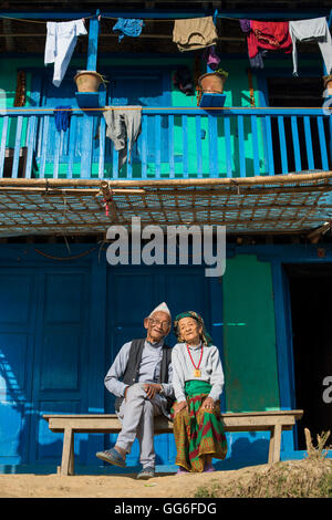 A old Nepali couple wearing traditional dress sit outside their house in Diktel, Khotang District, Nepal, Asia - Stock Photo