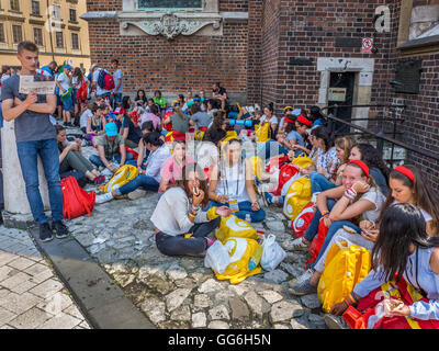 World Youth Day 2016. Young pilgrims from various countries sitting on the ground, resting, eating talking in the - Stock Photo