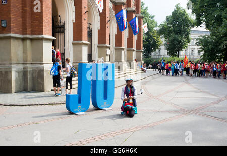 World Youth Day 2016: A girl making a selfie and other young pilgrims in front of the Collegium Novum of Jagiellonian - Stock Photo