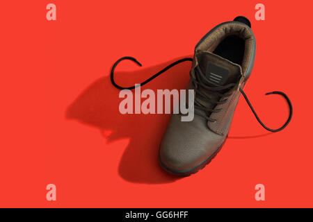 Brown safety boots over a red background - Stock Photo
