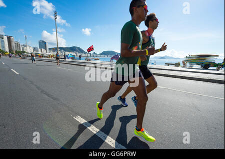 RIO DE JANEIRO - APRIL 3, 2016: A pair of joggers take advantage of a car-free Sunday morning on the beachfront - Stock Photo