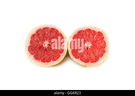 grapefruit split in two halves, outside yellow, red interior, on white background - Stock Photo
