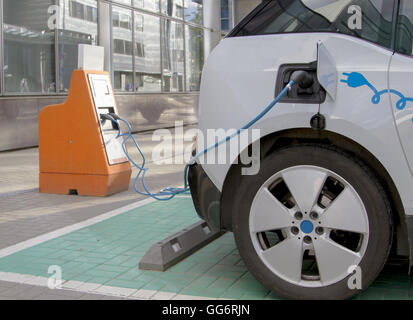 Electric car charging station. Close up of the power supply plugged into an auto being charged. - Stock Photo