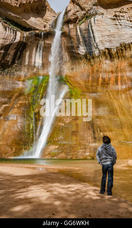 Boy looking at Lower Calf Creek Falls, Grand Staircase-Escalante National Monument, Utah, USA - Stock Photo