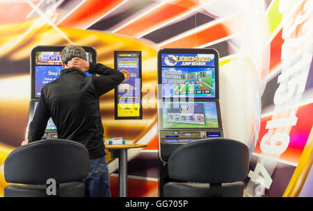 Mature man using fixed odds Roulette machine (FOBT fixed odds betting terminal) in Bookmakers. England, UK - Stock Photo
