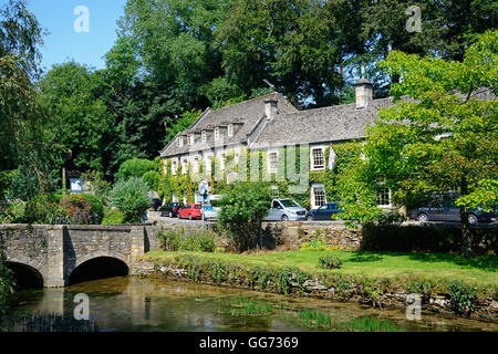 View along the River Coln towards the stone bridge with The Swan Hotel to the rear, Bibury, Cotswolds, Gloucestershire, - Stock Photo