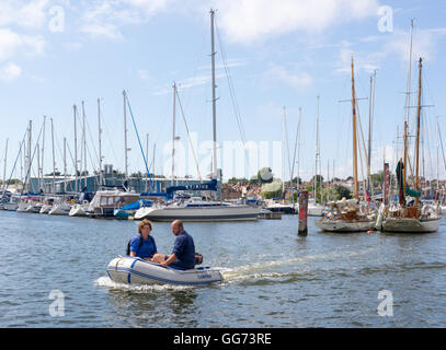 A couple use a dinghy to get to their off-shore moored boat in the sunshine at Lymington Hampshire UK. - Stock Photo