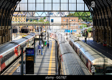 Trains stop at the platforms in Kings Cross train station - Stock Photo