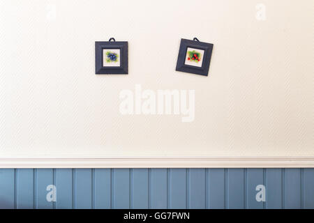 Two small square pictures of blueberries and strawberries in frames hanging on the white blue wall. - Stock Photo