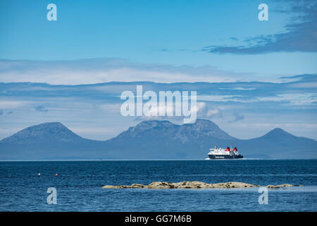 View of The Paps of Jura mountains on the Island of Jura and CalMac passenger ferry from Kintyre Peninsula in Argyll - Stock Photo