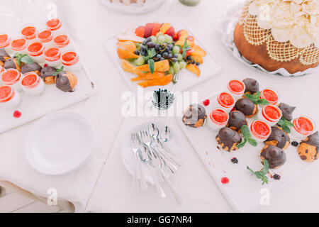 Elegant sweet table with cupcakes, cake pops on dinner or event party - Stock Photo