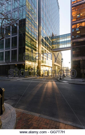 Early morning sun reflects off tall building on quiet sidestreet - Stock Photo