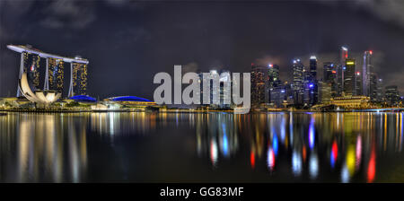 Marina Bays with the Sands hotel and the central business district taken at night colourful reflection - Stock Photo