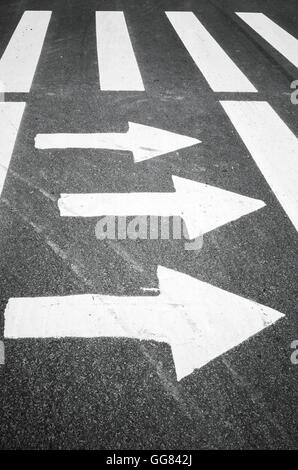 White arrows and stripes over black asphalt road, pedestrian crossing road marking zebra - Stock Photo