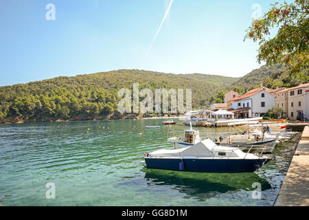 Cres Island, Croatia: View to the village Valun with harbor and boats in the evening sun - Stock Photo