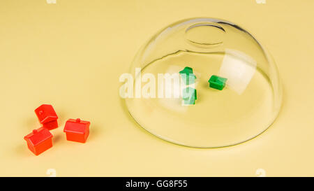 real estate insurance, three green miniature plastic houses protected and three red houses not protected with a - Stock Photo