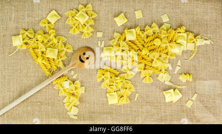 map of the world made of raw pasta on brown fabric background with texture with wooden smiling scoop - Stock Photo
