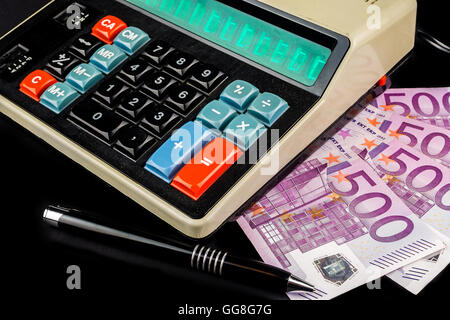 retro style calculator with a pen and big euro banknotes on black background - Stock Photo